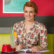 Attractive young woman writting a note in cafe — Stock Photo #25027539