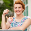 Attractive young woman eats ice cream outdoors — Stock Photo