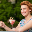 Attractive young woman eats ice cream outdoors — Stock Photo #25028599