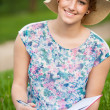 Attractive young woman with a hat studies on a meadow — Stock Photo