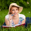 Stock Photo: Attractive young womwith hat studies on meadow