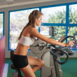 Beautiful skinny woman riding a bike in fitness — Stock Photo