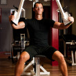 Active sportsman works out in fitness on butterfly machine — Stok fotoğraf