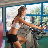 Beautiful skinny woman riding a bike in fitness — Stock Photo