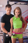 Active young woman works out with coach — Stock Photo