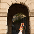 Portrait of bride and groom under stone arch — Foto Stock