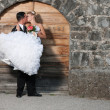 Groom holding a bride infront of wooden door — Stock Photo