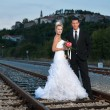 Bride and groom on a railway at dusk — Stock Photo #32632703