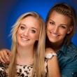 Two beautiful girls smiling over blue studio background — Stock Photo