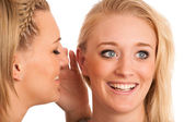Girls chat - woman whispers on friends ear — Stock Photo
