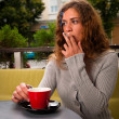 Young woman drinking coffee and smoking cigarette — Stock Photo #33104143