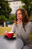 Young woman drinking coffee and smoking cigarette — Stock Photo