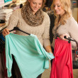 Womans shopping - Two girls in a clothes shop choosing garment — Stock Photo