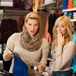 Stock Photo: Two girls shocked by a price of clothes in a shop