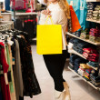 Young happy woman with shopping bags leaving a shop after purchase — Stock Photo