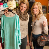 Womans shopping - Two girls in a clothes shop choosing garment — Foto de Stock