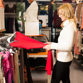 Young woman choosing a garment in a shop — Stock Photo