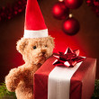 Teddy bear with red santa claus hat and christmas presents — Stock Photo