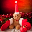 Plush bear with red christmas  gloves and red ball — Stock Photo
