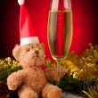 Plush bear with glass of sparkling wine on christmas decoration — Stock Photo
