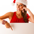 Beautiful young woman in red santa claus dress pointing to red b — Stock Photo #34625965