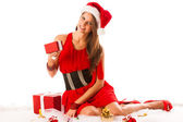Beautiful young woman in santa claus dress sitting on the flor i — Stock Photo