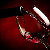 Bottle filling the glass of wine - splash of delicious flavor. — Stock Photo