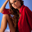 Pensive young woman in red shirt sitting in bed on white silk sh — Foto de Stock
