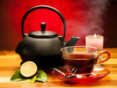 A cup of black tea with teapot in the background — Fotografia Stock