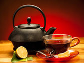 A cup of black tea with teapot in the background — Stock Photo