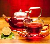 Uma xícara de chá quente com o bule no fundo em uma mesa de madeira — Fotografia Stock