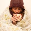 Ill woman with feaver drinking cup of warm tea under blanket — Stock Photo