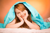 Woman iling on pillow in bed, covered with blanket — Stock Photo