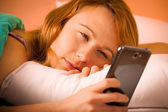 Preety woman reading a sms on cell phone in bed — Stock Photo