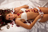 Beautiful young woman wearing white lingerie lying in bed of ros — Stock Photo