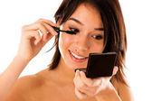 Pretty woman applying mascara on her eyelashes — Stock Photo