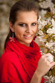 Beautiful young woman with red scarf in park with cherry blossom in early spring — Stock Photo