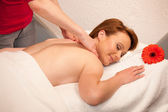 Beautiful young woman enjoing a massage treatment in wellness — Stock Photo