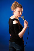 Woman singer on bluue background with microphone  — Stock Photo
