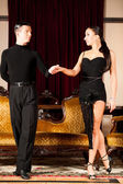 Young dance couple preforming latin show dance in ancient ballro — Stock Photo