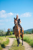 Beautiful young blonde woman riding a horse — Stock Photo
