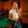 Beautiful young blonde woman playing billiard in a bar — Stock Photo #51119691