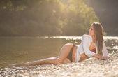 Preety woman in swimsuit near alpine river in early summer — Stock Photo