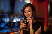 Girl drinks a cocktail in night club — Stock Photo