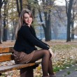Royalty-Free Stock Photo: Young woman is sitting on the bench in autumn park