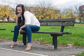 Young woman sitting on the bench — Stock Photo