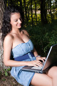 Smiling woman with laptop sitting under tree — Stock fotografie