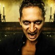 Male vampire with evil eyes - Stock Photo