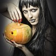 Woman witch holding pumpkin — Stock Photo #12675605