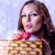 Young sexy woman santa with gift - Stock Photo